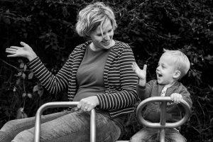 Moeder en zoon op speeltoestel zwaaien